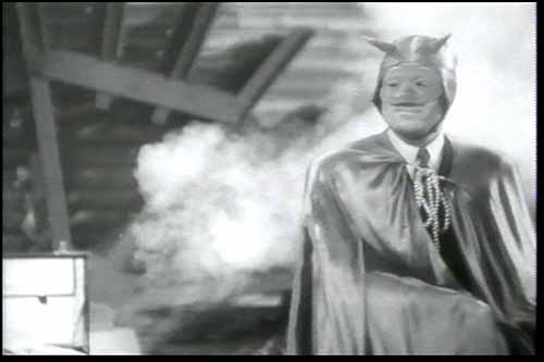 Mandrake is disguised in a magician's mask, hood, and cape with a clear devil motif. This is not his outfit, but one he wears to impersonate the criminal magician named Regan
